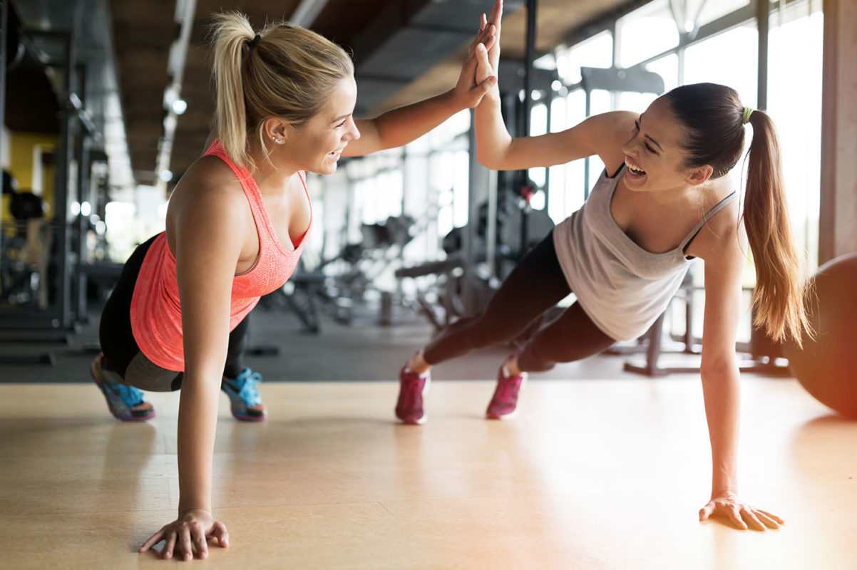 Two women high-five in fitness center while doing planks with cardio and weight machines in background