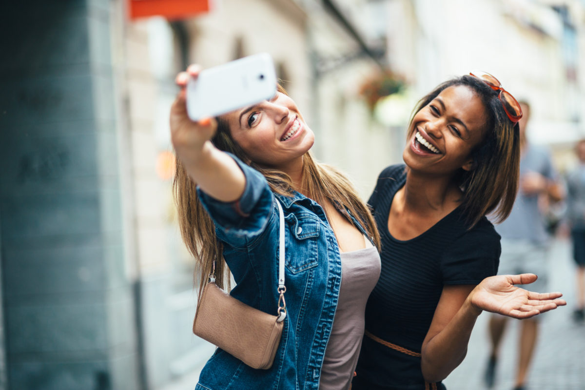 Two women laughing and taking a selfie outdoors