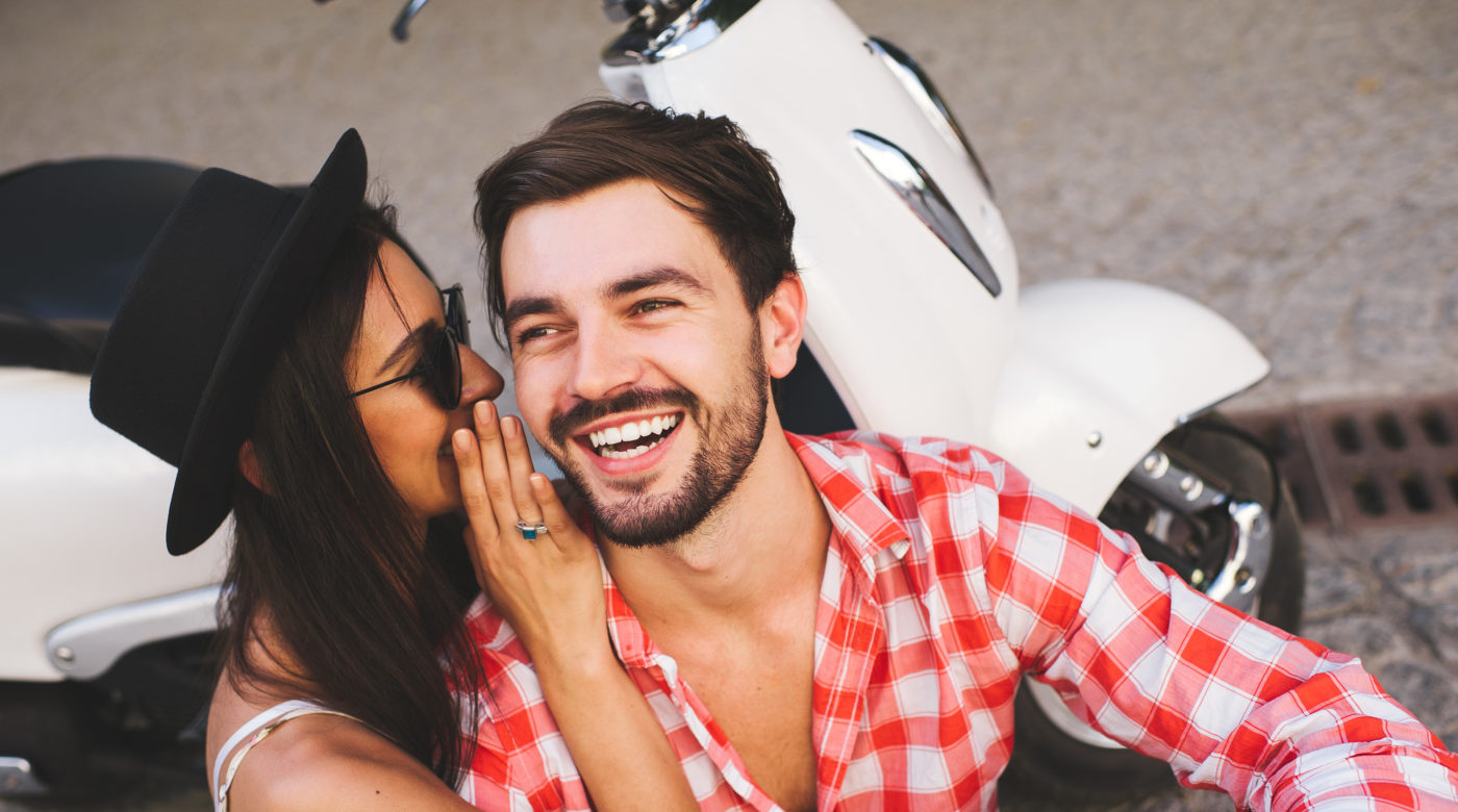 Woman whispering to laughing man with parked scooter behind them