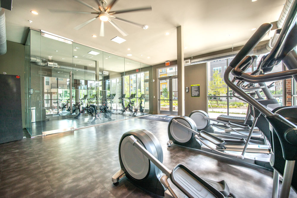 Fitness center with cardio elliptical machines, large mirrored wall and large ceiling fan