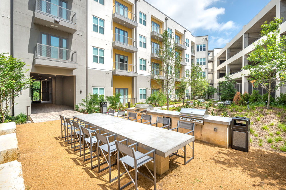 Outdoor seating area with large family style table and outdoor grills
