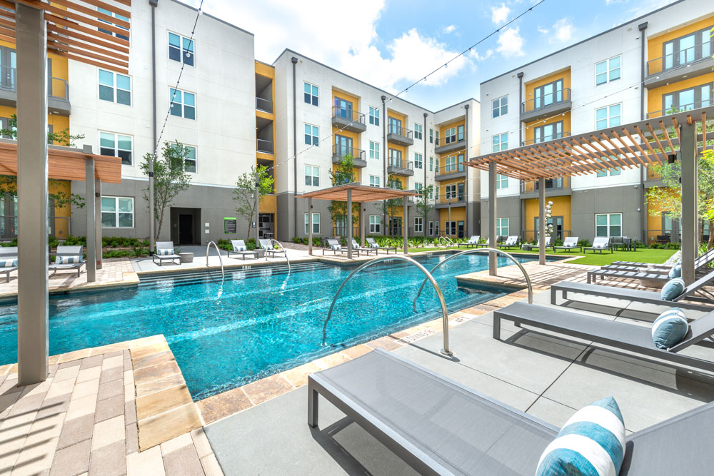 Resort style pool with lounge seating and safety rails