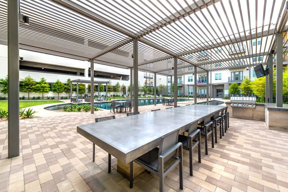 Outdoor kitchen with grills and covered family style seating table