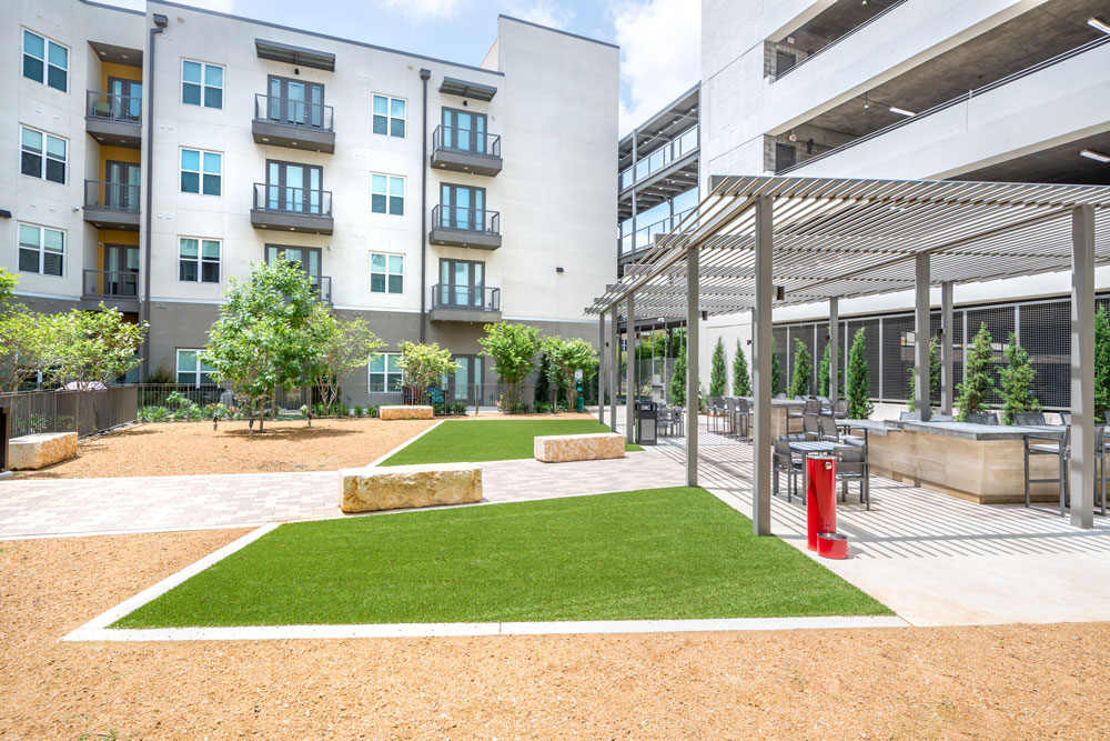 Gated dog park with obstacles, seating, gravel and turf areas and a water fountain