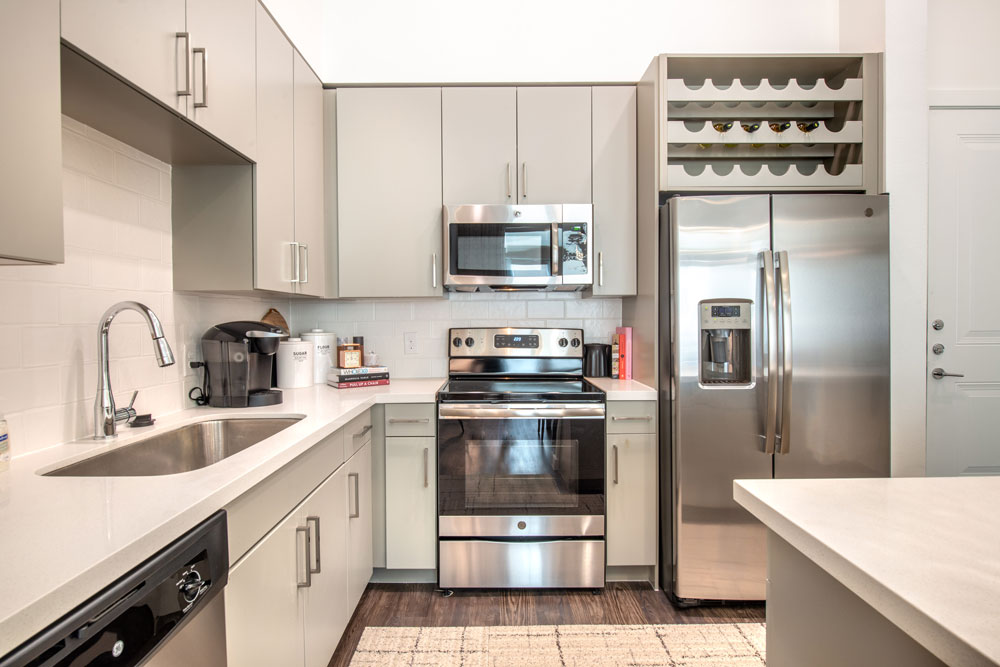 Kitchen with plank flooring, stainless steel appliances, quartz countertops and island