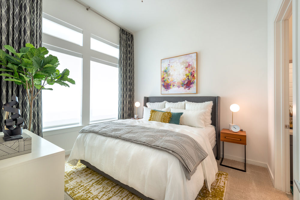 Bedroom with plush carpeting, ceiling fan, large windows for natural light and door to private Bathroom