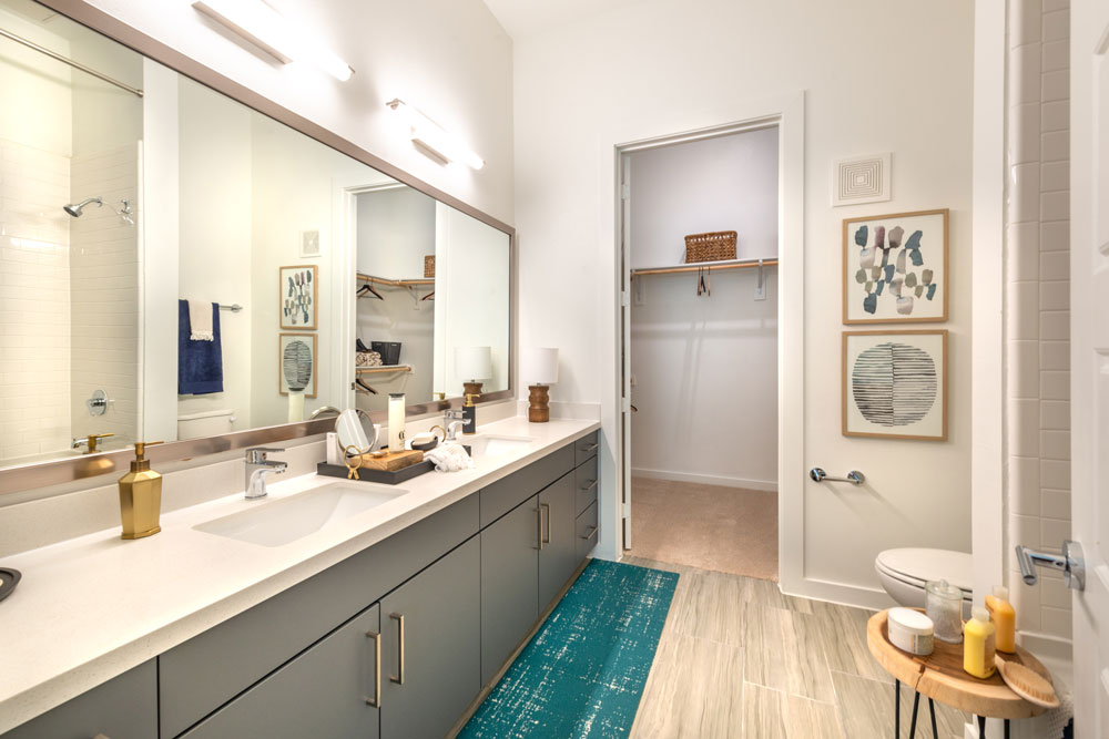 Bathroom with dual sinks quartz counters, tub/shower, walk-in closet, and framed mirror