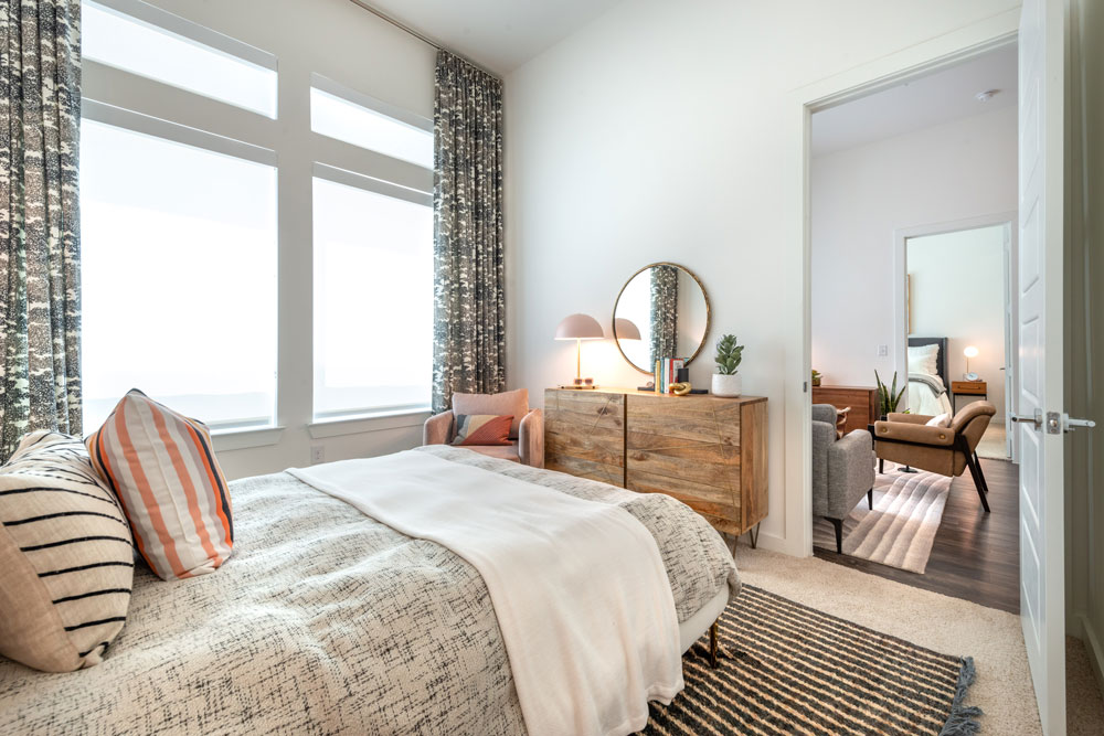 Bedroom with dual large windows, queen sized bed and modern furniture and plush carpet
