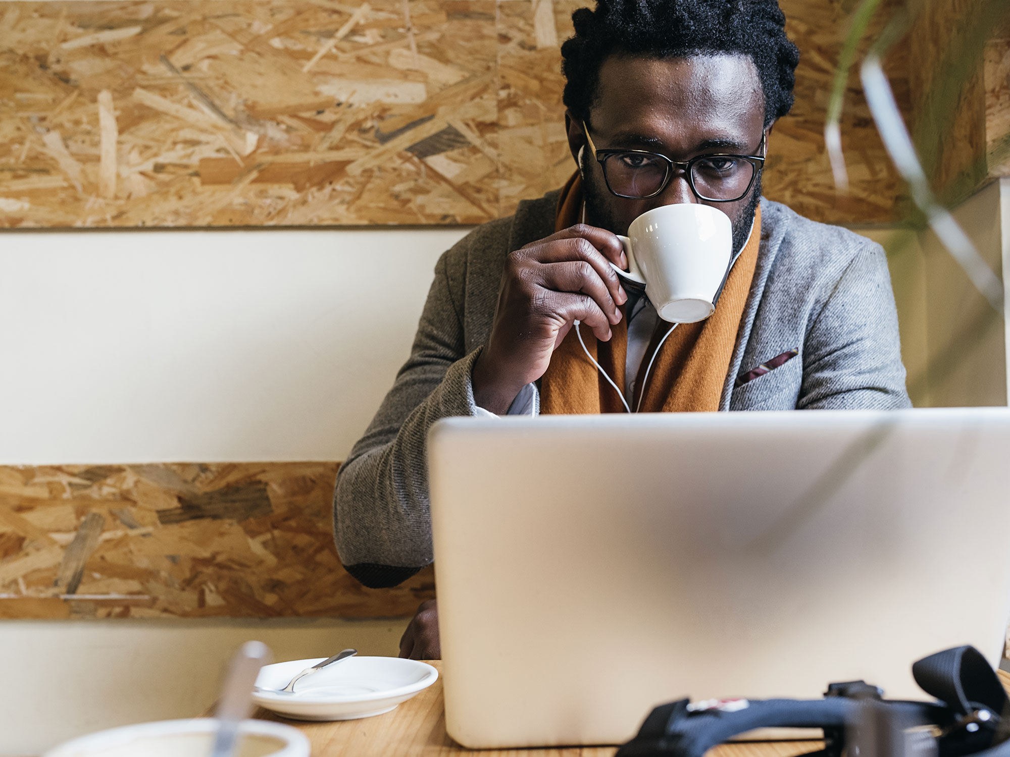 Man sipping espresso while on his laptop