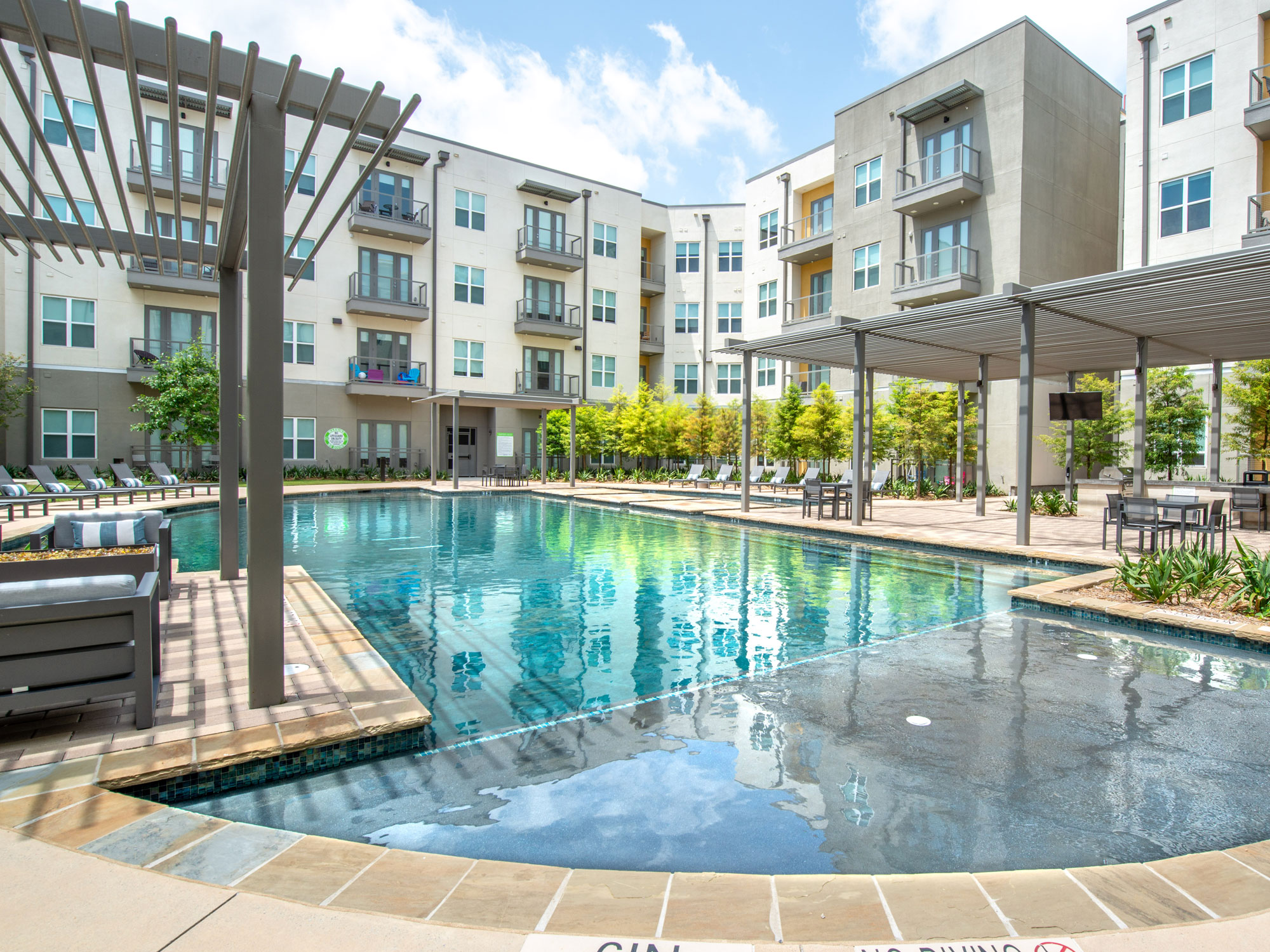 Resort style pool with tanning ledge, covered plush seating, lounge chairs and professional landscaping
