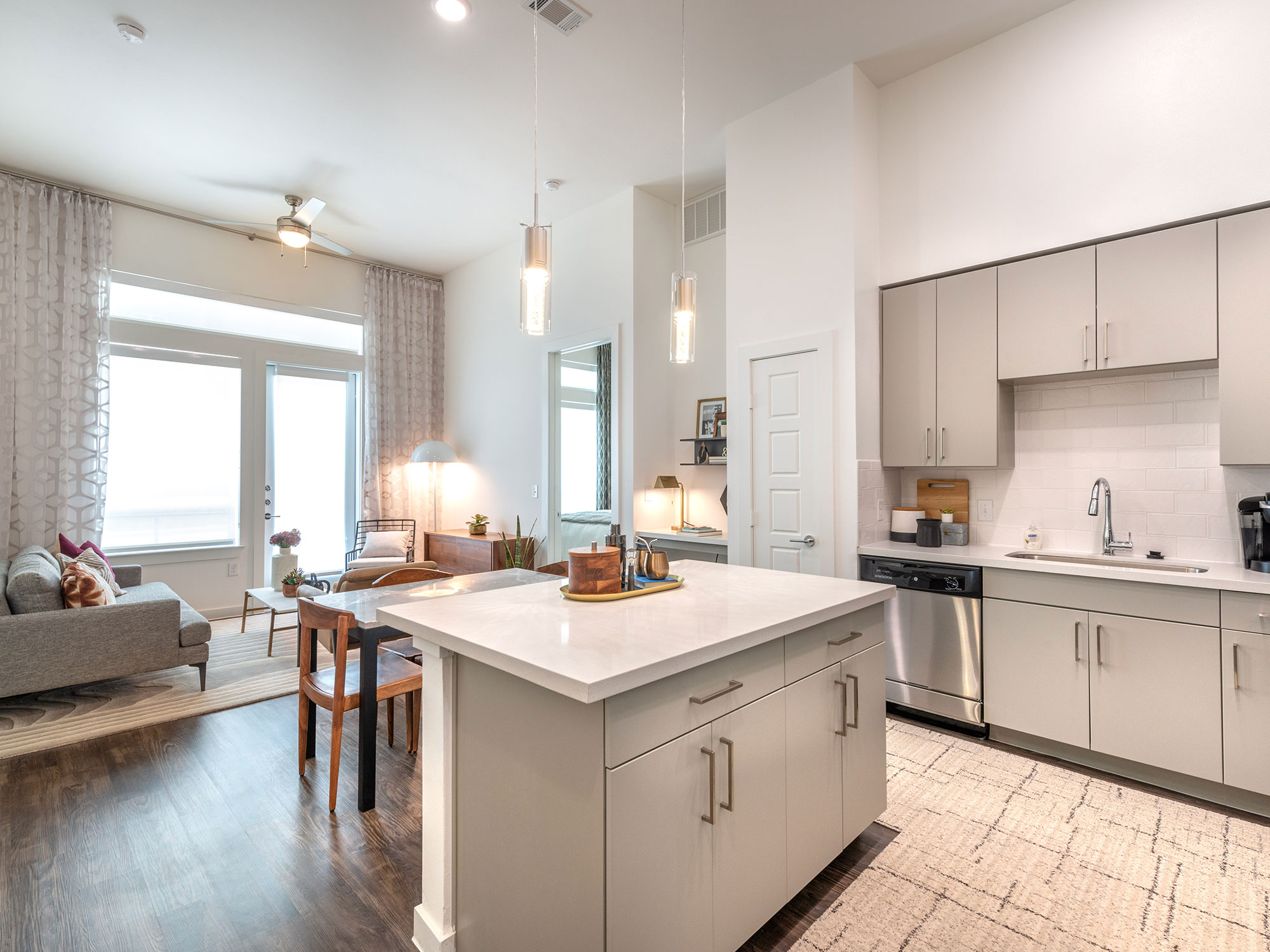 Apartment interior with plank flooring, modern kitchen with stainless steel appliances and designer lighting, and living room with built-in desk and a door leading to patio