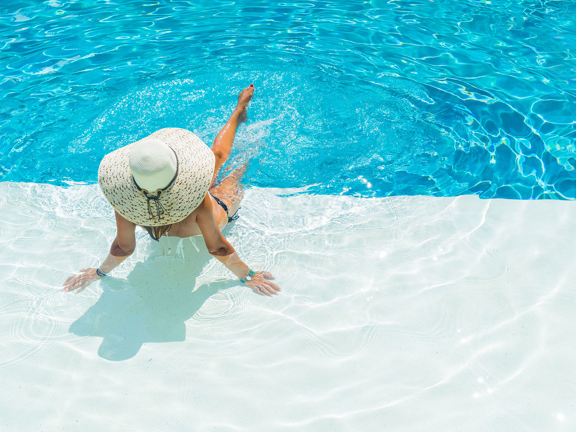 Woman in large hat sitting on tanning ledge of pool