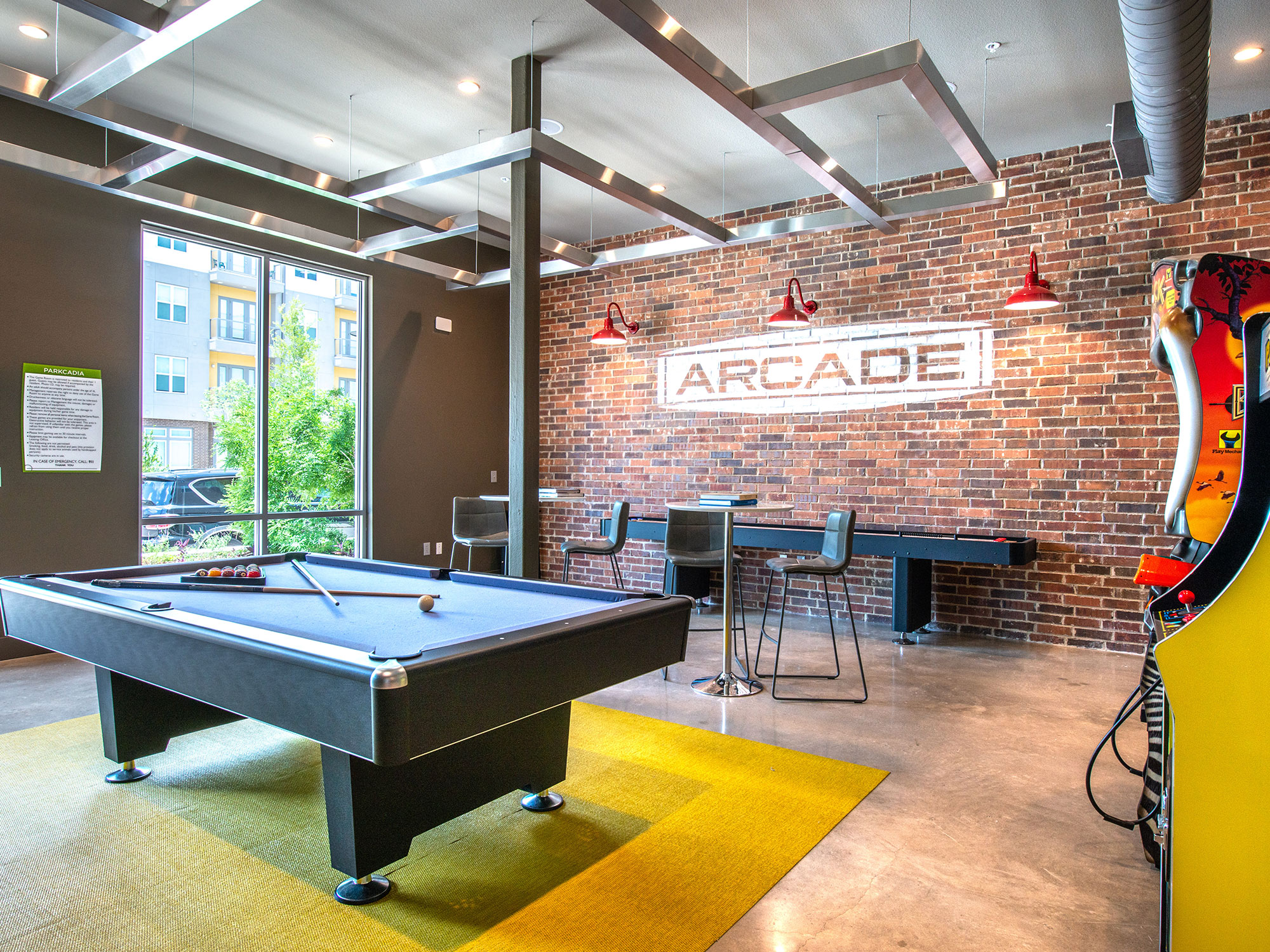 Clubhouse interior with shuffleboard, arcade games pool table and high bar seating