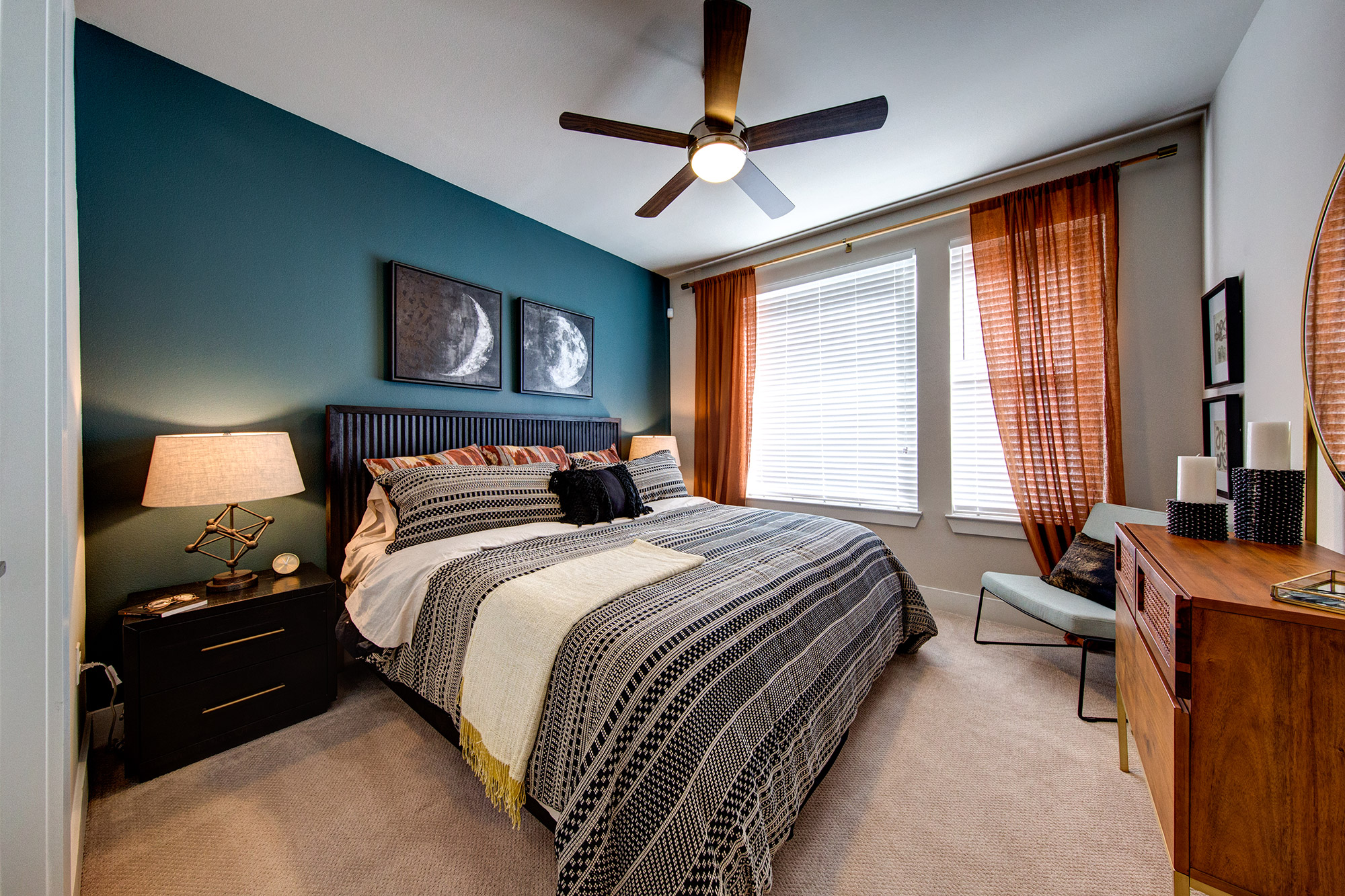 Bedroom with large windows, plush carpeting, ceiling fan, accent wall and modern bedroom furniture.