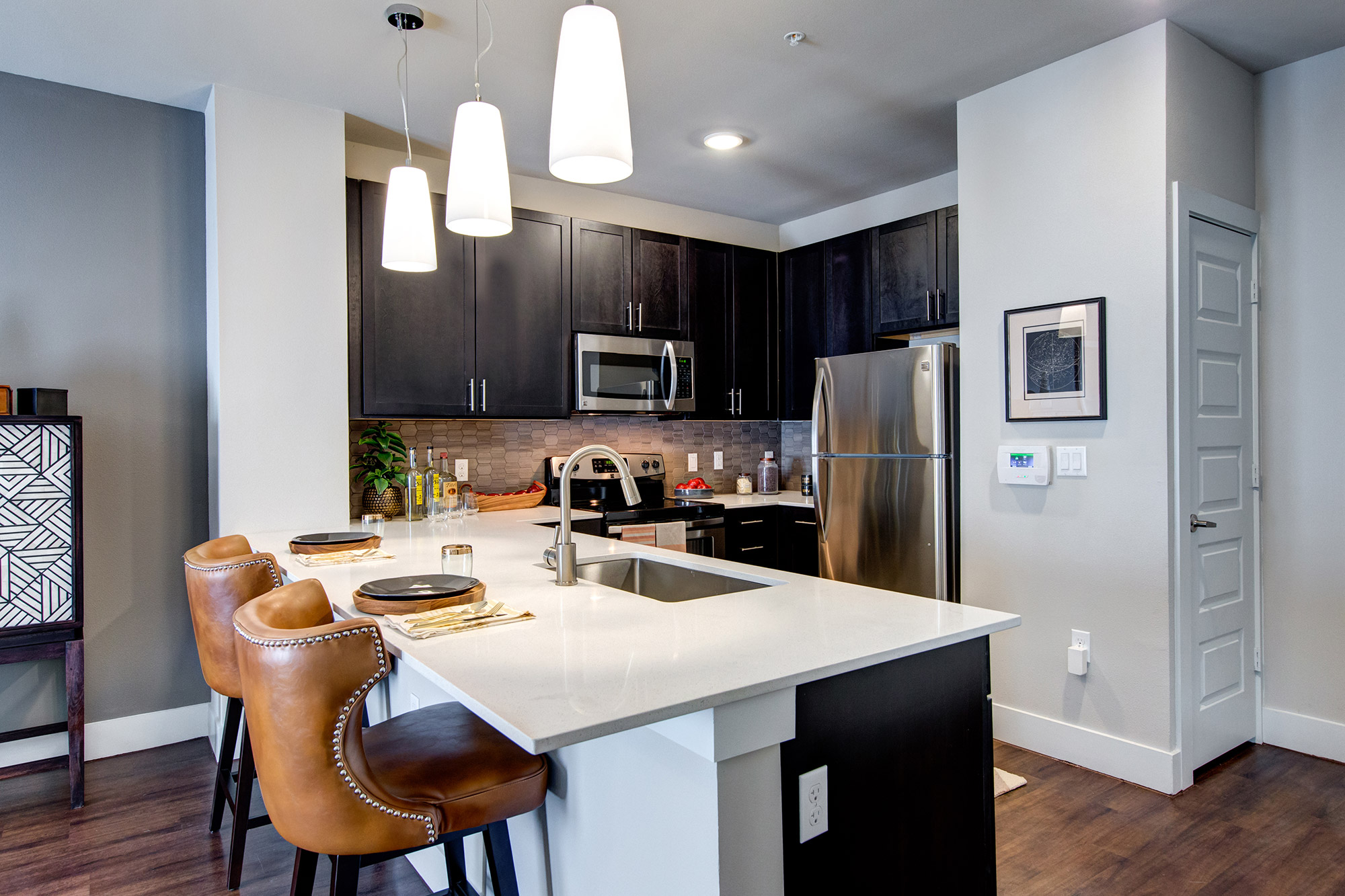 Kitchen with quartz counters and bar style seating, stainless steel appliances, pantry and designer lighting