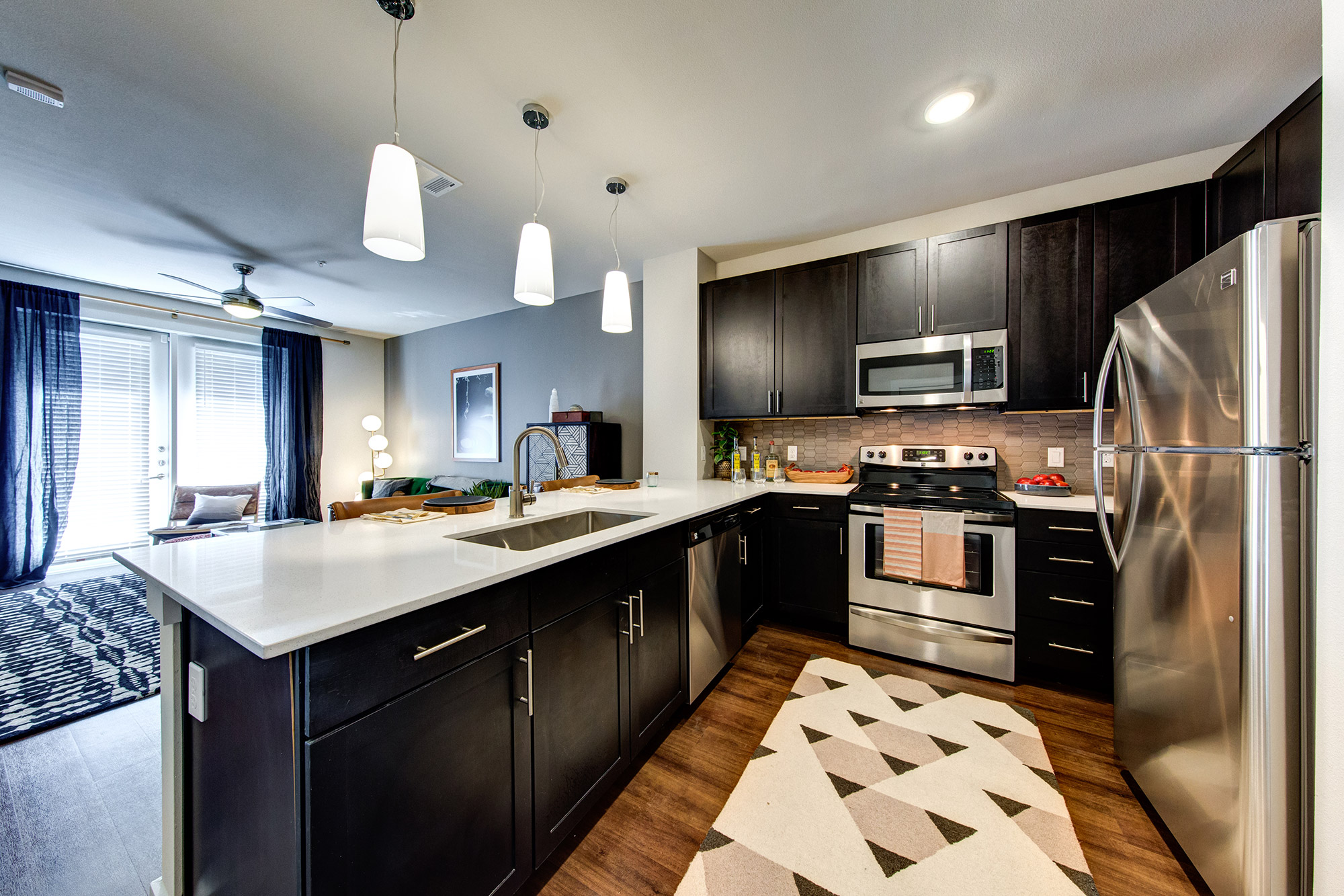 Kitchen with black cabinetry, wood-style floors, stainless steel appliances and quartz countertops that is open to the living room with double patio doors.