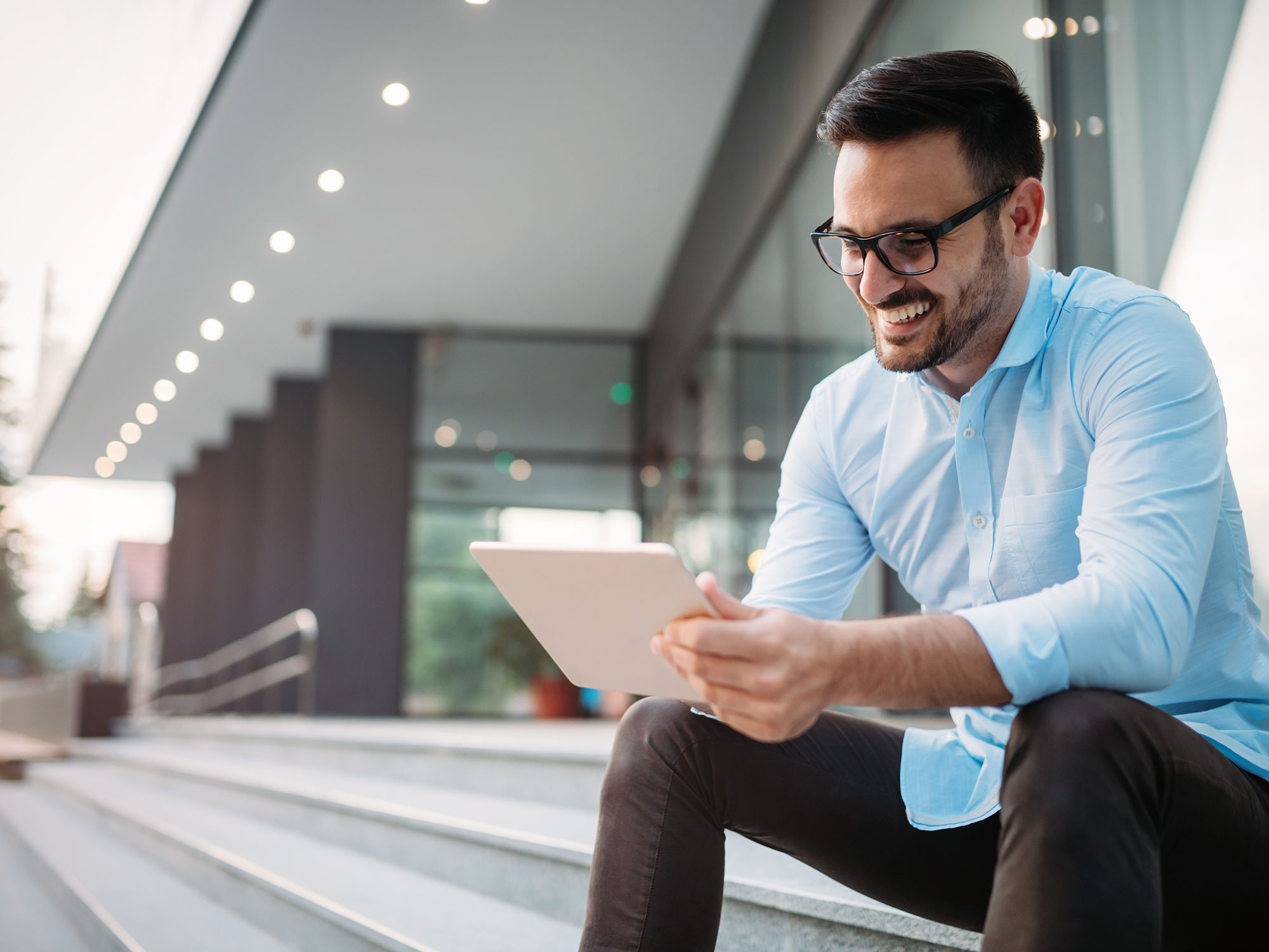 Business man looks at a laptop sitting outdoors on stairs