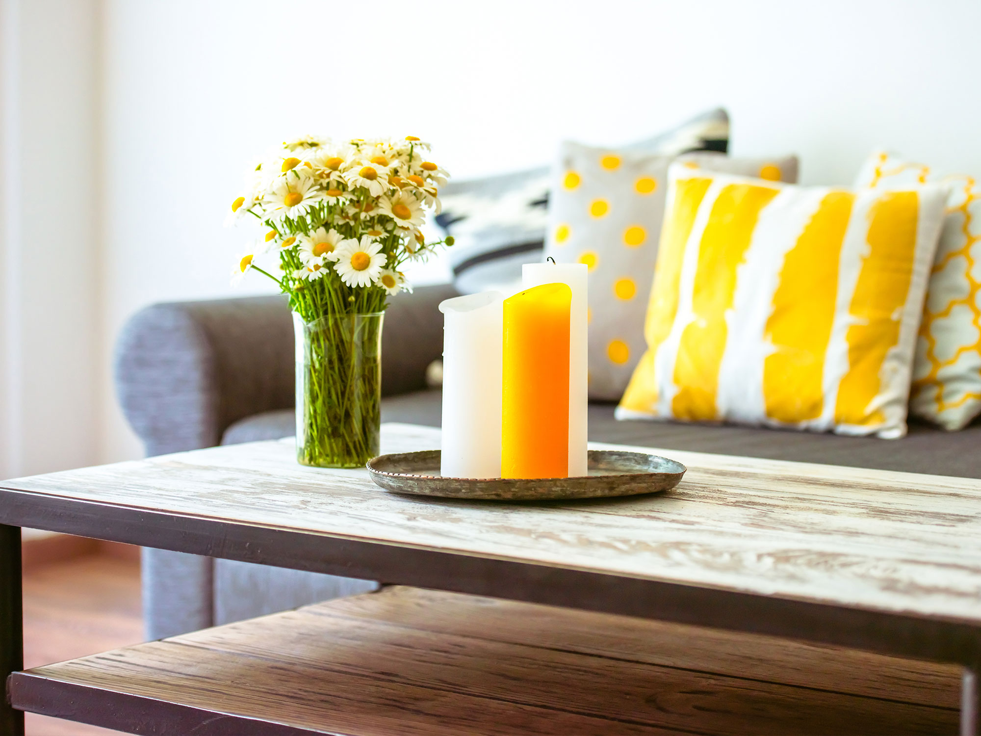 Coffee table with flowers and candles with couch in the background