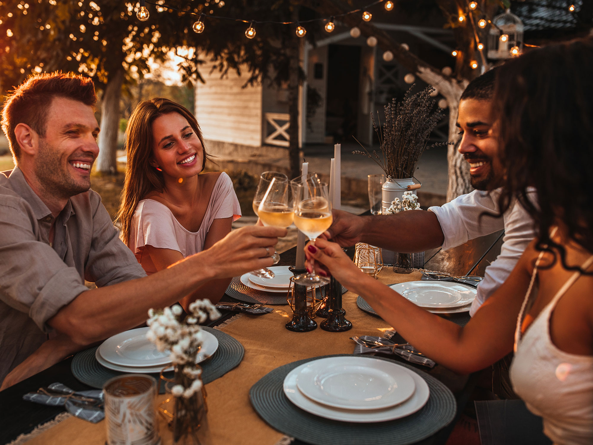 Diverse friends cheers with wine glasses at outdoor restaurant