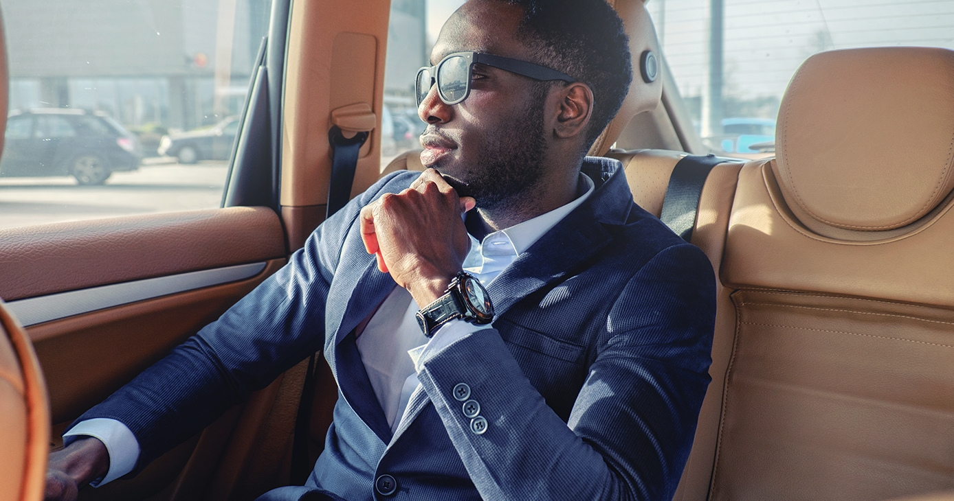 Man in suit and sunglasses in a car looking out window