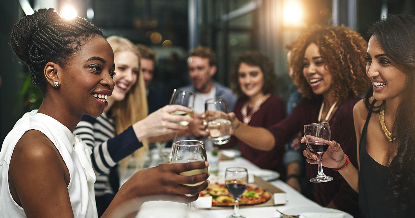Diverse group of friends toast at restaurant with wine