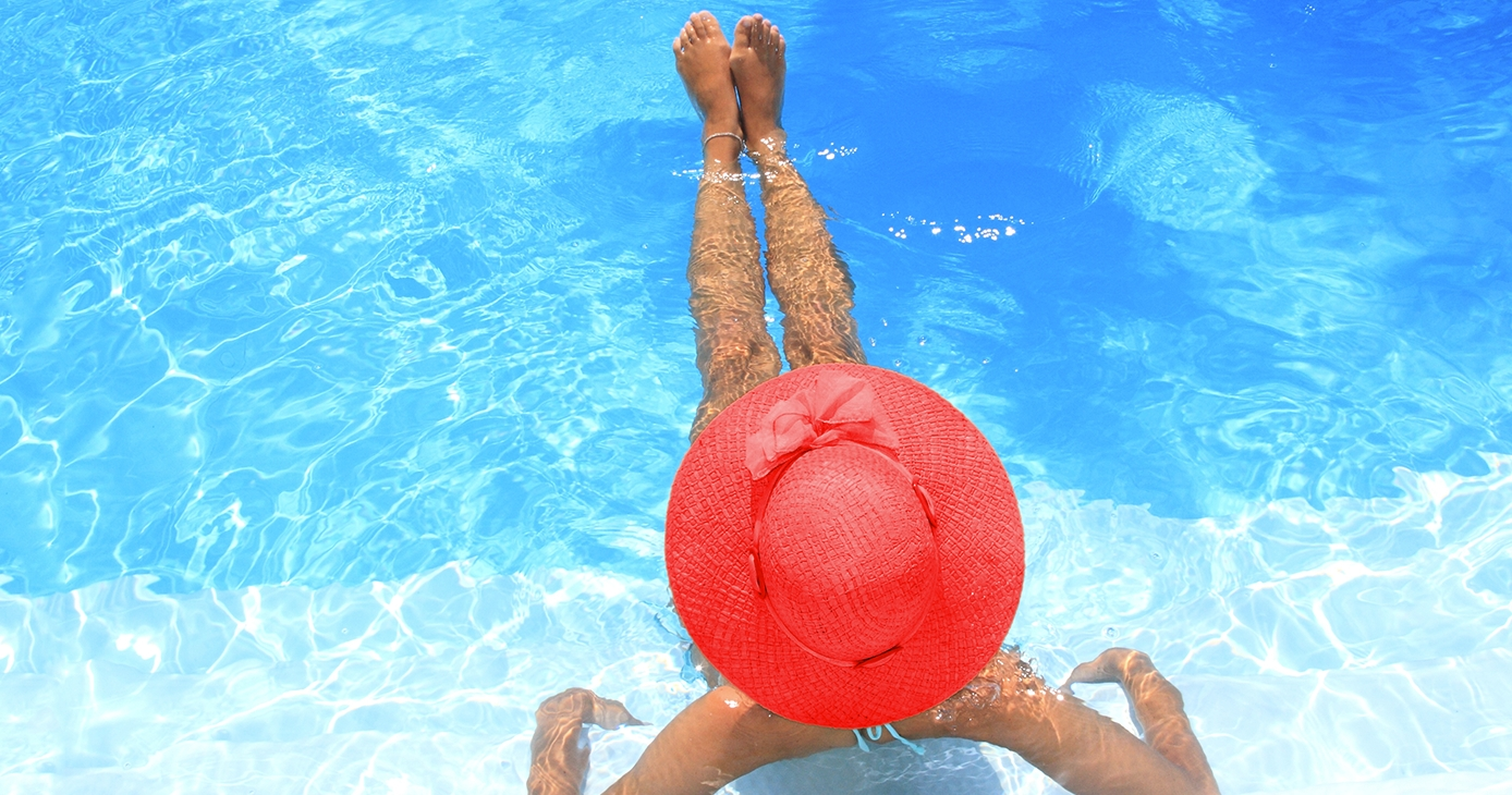 Woman lounging in a pool wearing a red hat