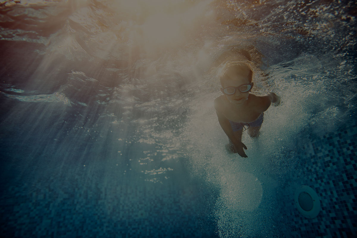 Young boy swimming in pool viewed from underwater
