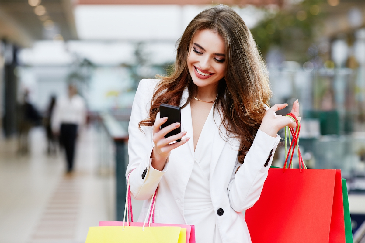 Young woman looking at phone while holding many shopping bags