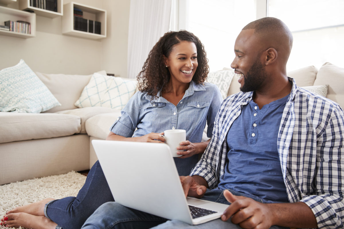 Couple sitting on the ground in front of couch talking, while holding a computo