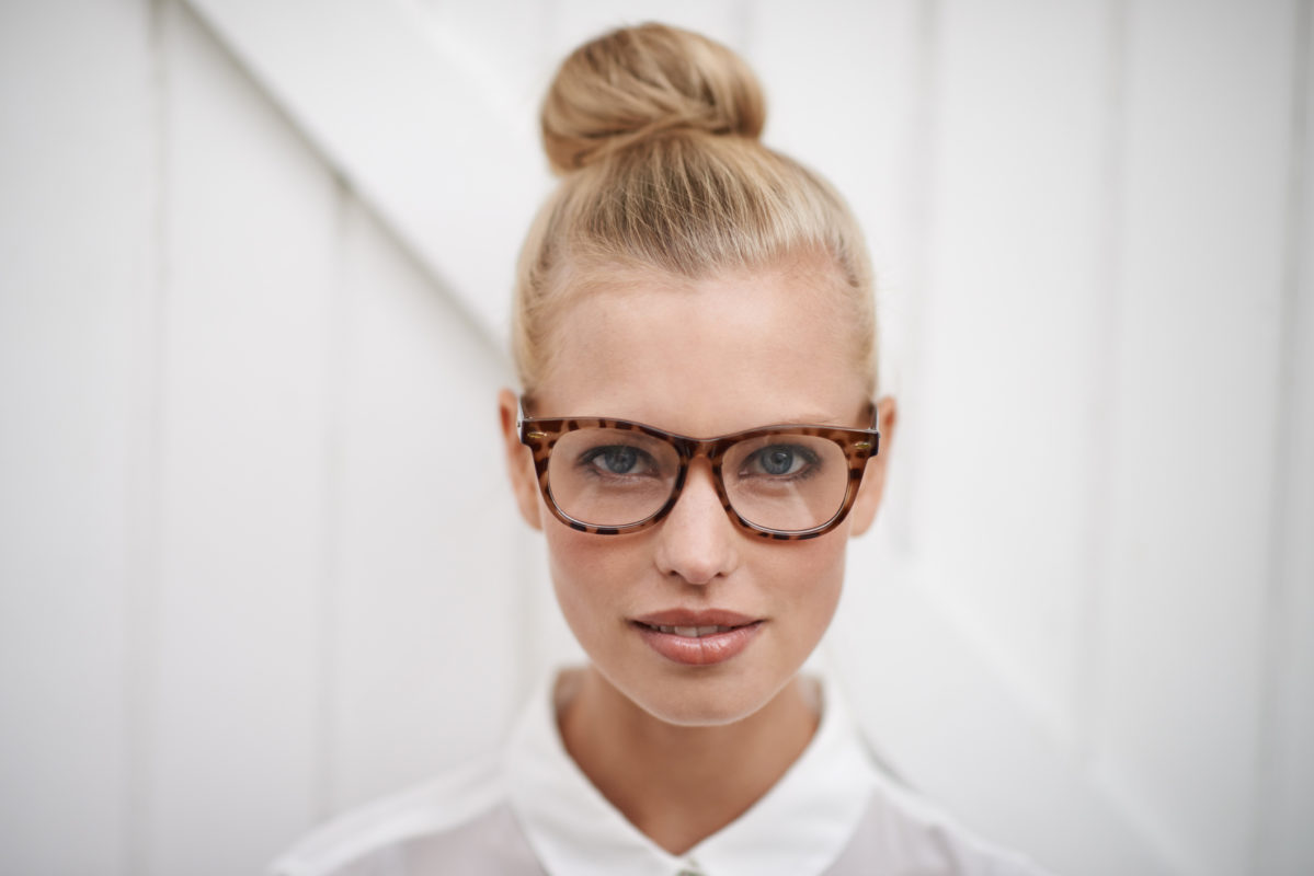 A young woman wearing a blouse and spectacles