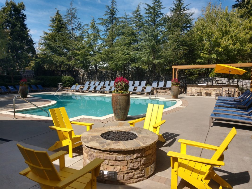 Yellow chairs around a poolside fire pit