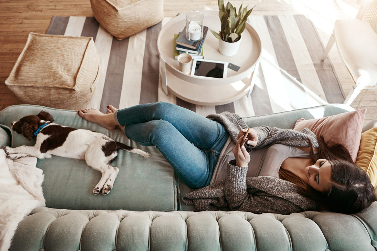 Living room with wood floor, coffee table and woman laying on couch with dog, texting on phone