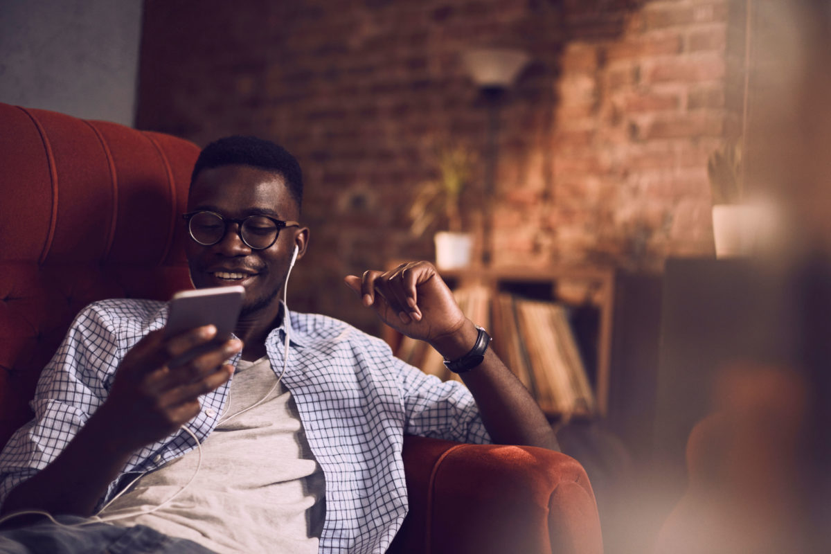Young man on couch looking at phone with headphones
