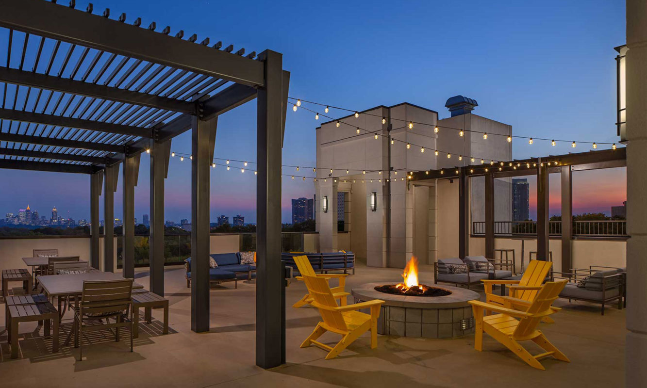 Dusk shot of rooftop fire pit with string lighting and tables and chairs