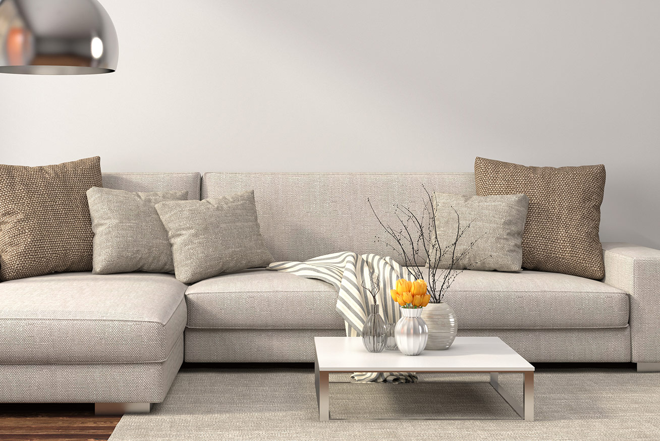 high-end grey couch with pillows and small coffee table with decorative plants