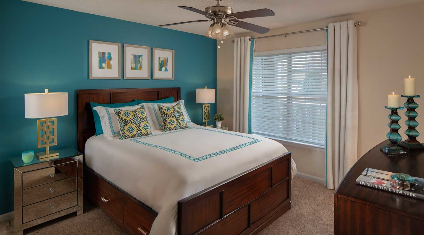 bedroom with ceiling fan, large window, teal accent wall, and dark wood furniture
