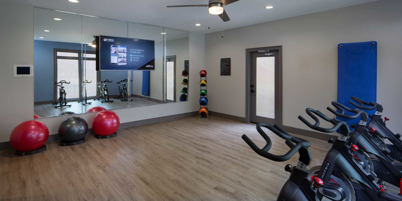 yoga center with pilates balls, tv, mirror, and bikes