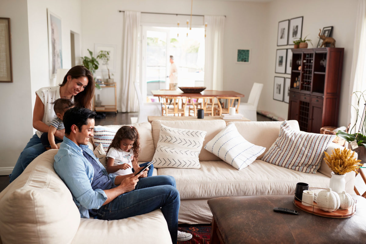family on living room couch with tablet