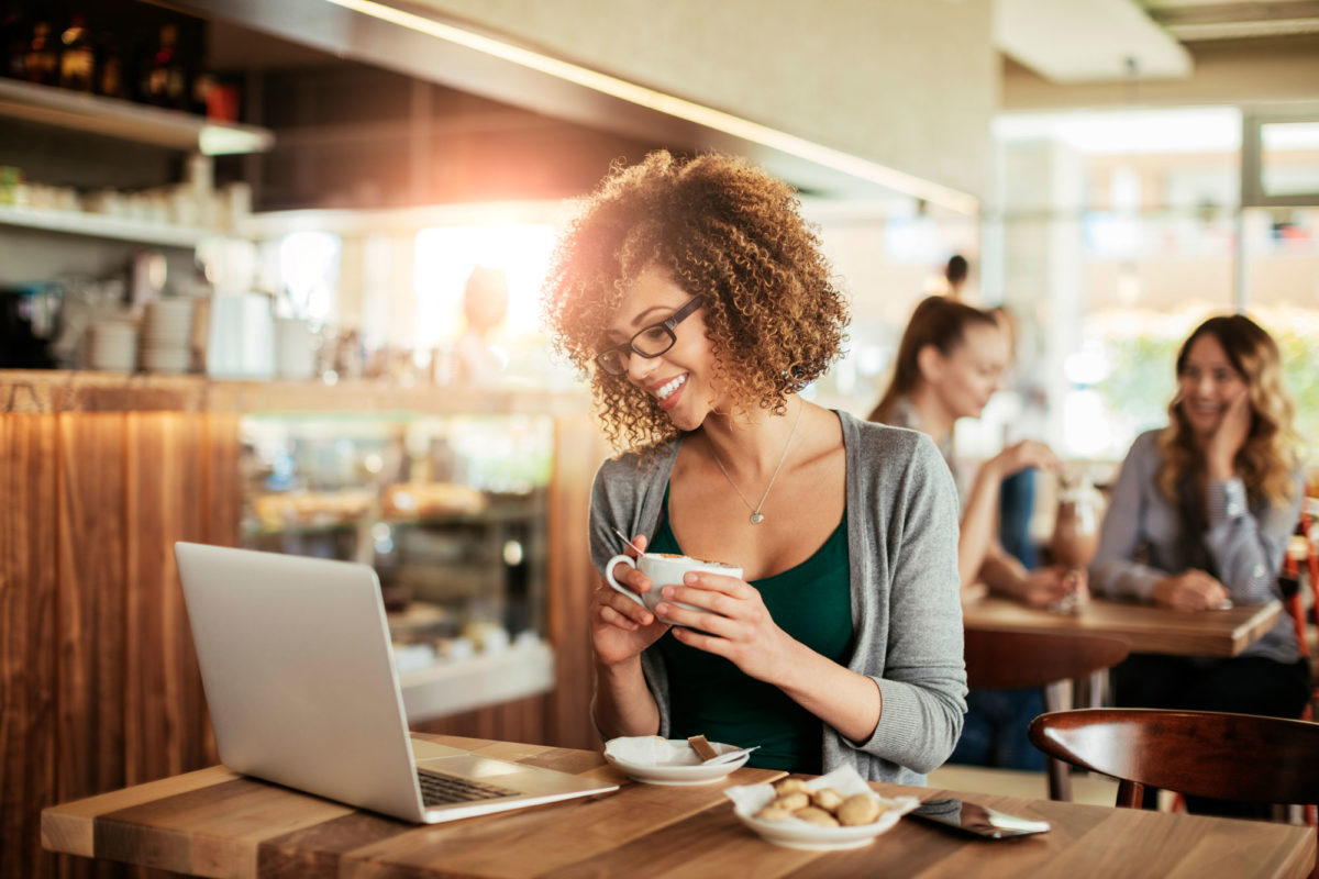 smiling woman at coffee shop with computer drinking coffee