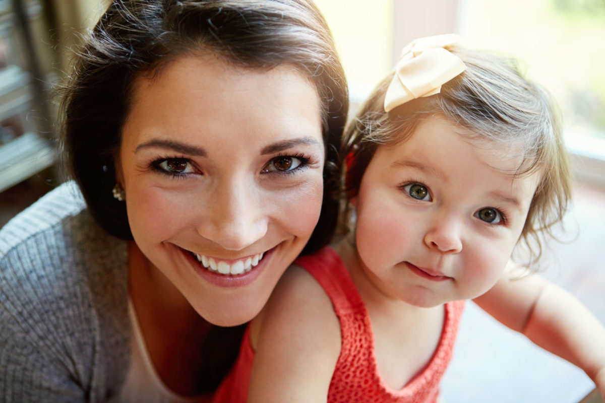 woman smiling with her baby daughter