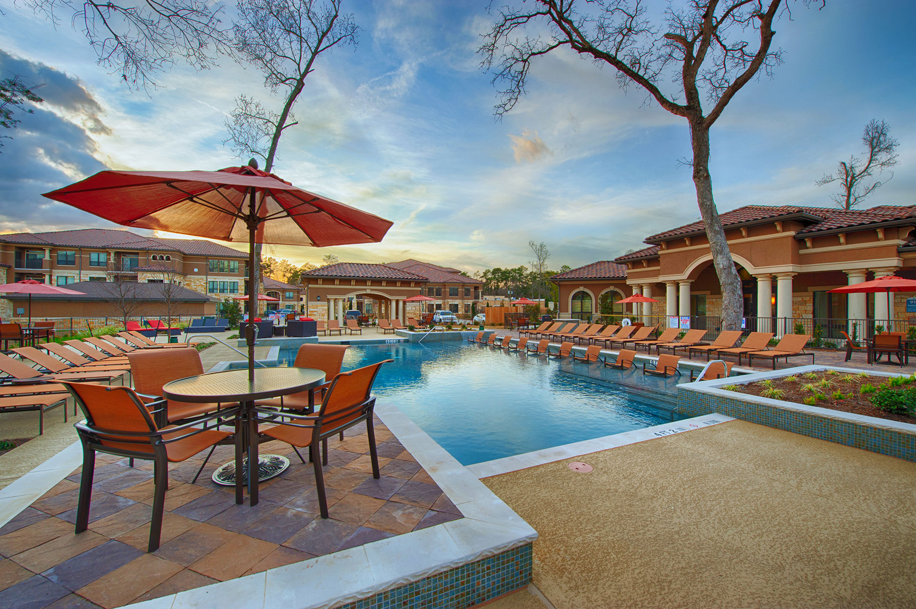 sunset view of rectangular pool with patio seating