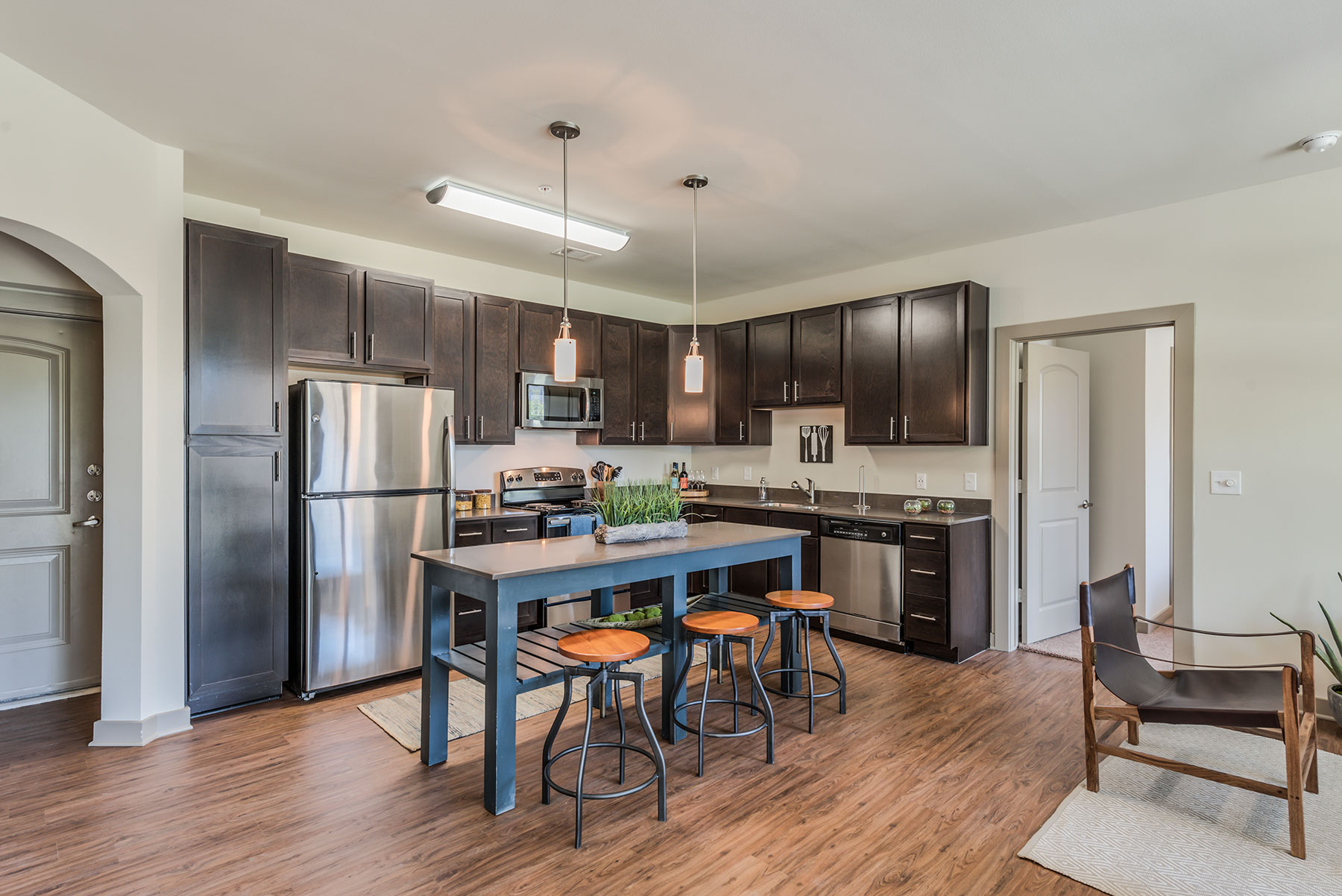 kitchen view with dark wood cabinets, stainless steel appliances, bar-style table and seating and granite countertops