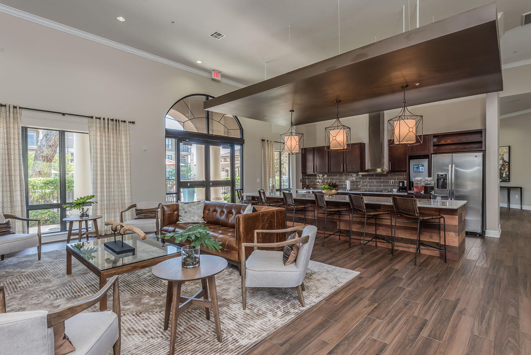expansive clubhouse kitchen with bar top seating, large windows and comfortable seating for socializing