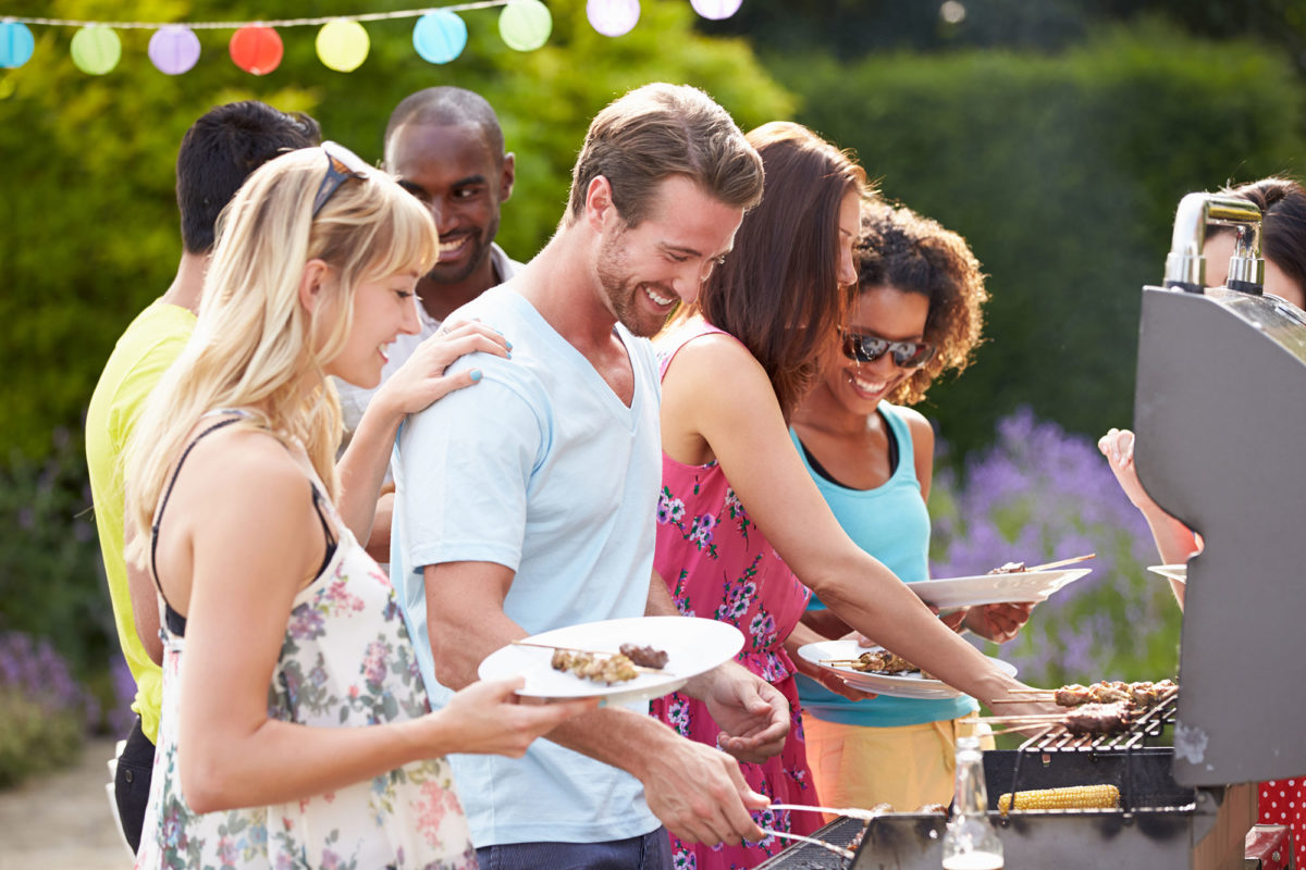 group of adult friends grilling outdoors