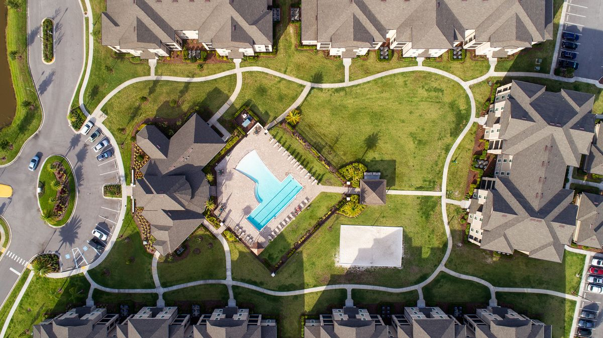 High up overhead view of the community showing apartment buildings that surround the clubhouse, pool courtyard, and sand volleyball court