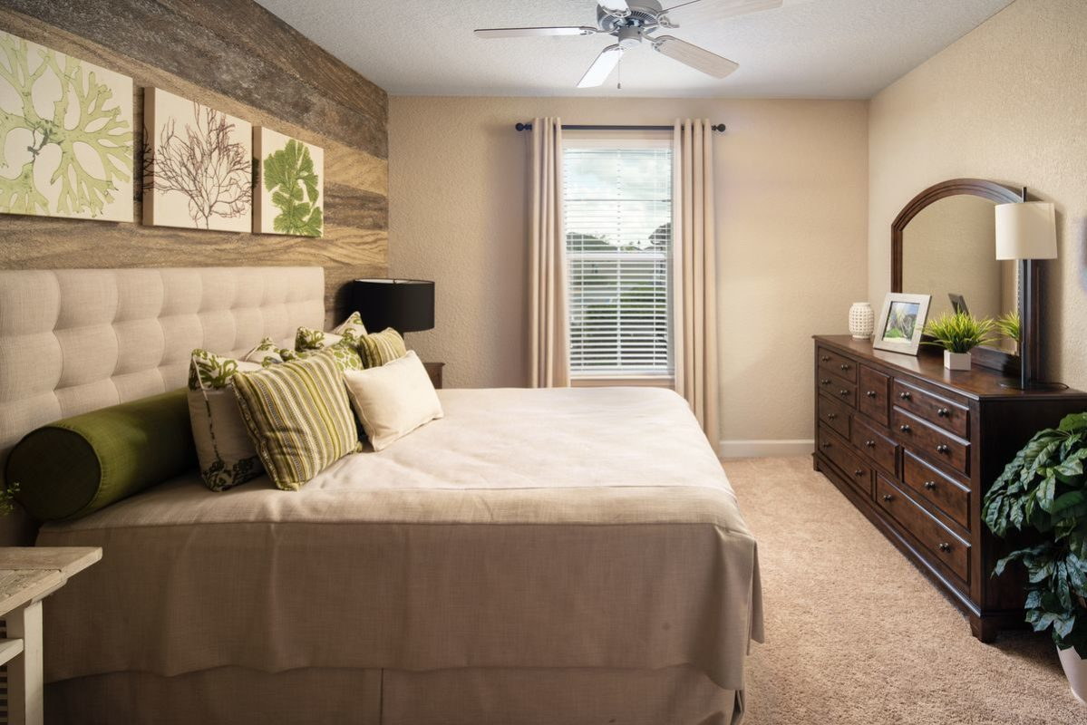 Furnished bedroom with carpet floor, ceiling fan with light, and one window