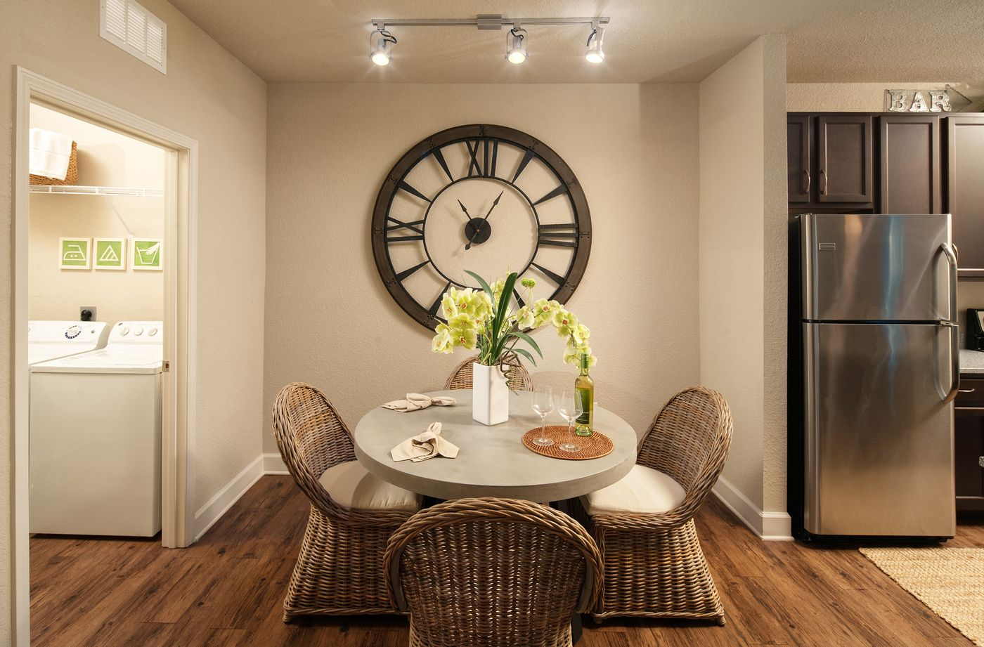 Furnished apartment dining room with laundry room and kitchen on either side, wood flooring and track lighting