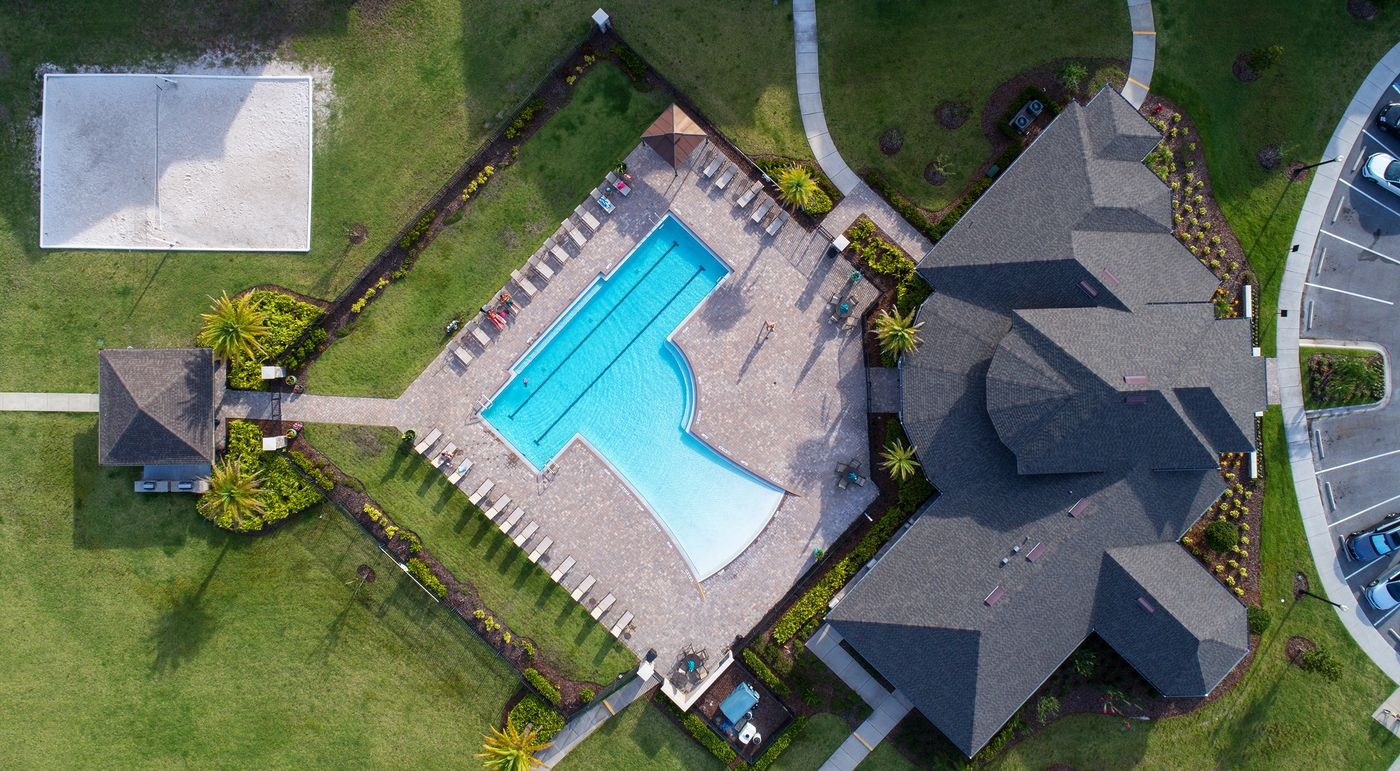 Aerial overhead view of the pool courtyard, sand volleyball court, and clubhouse