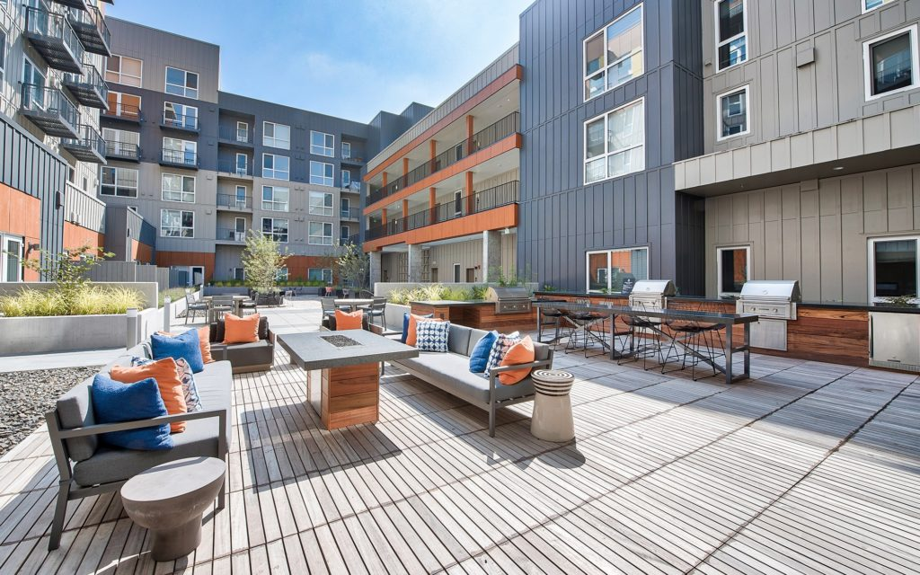 Outdoor courtyard with lounge seating and tables, a fire table, grilling stations and a high-top dining table with bar stools.