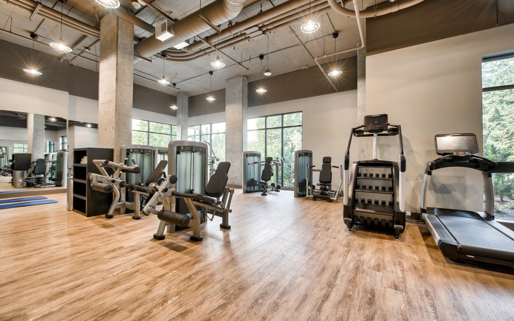 Fitness center with wood flooring, mirrored walls, exposed pipe ceiling, and weight machines, branches and treadmills.
